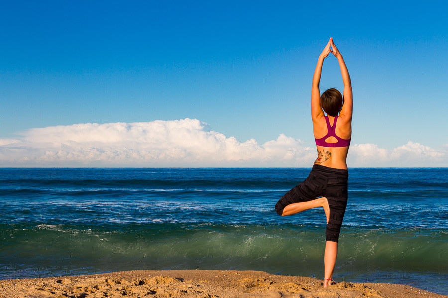 Shooting Young woman makes Yoga on a Beach